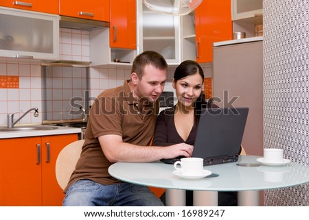 casual couple happy in their kitchen - stock photo