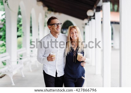 Casual couple having coffee together while walking outdoor - stock photo