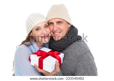 Casual couple in warm clothing holding gift on white background