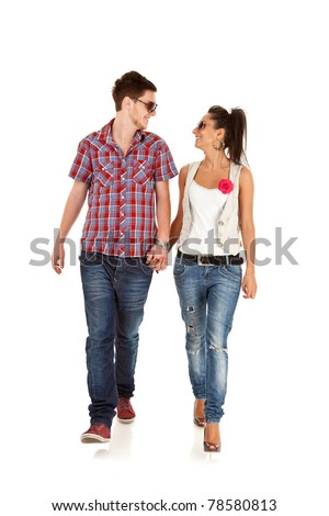 Casual couple is walking towards the camera  on White, looking at each other - stock photo