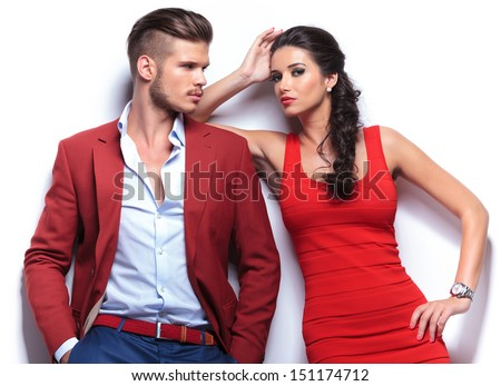 casual couple leaning against a white wall, man with hands in his pockets looking at the woman . woman looking at the camera while leaning on his shoulder - stock photo