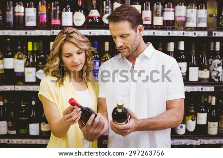 Casual couple looking at wine bottle in supermarket - stock photo