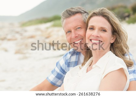 Casual couple smiling at camera at the beach