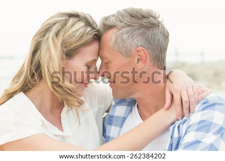 Casual couple smiling at each other at the beach - stock photo