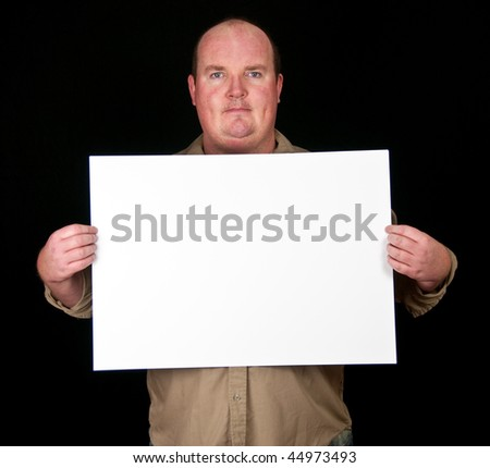 casual fat man holding an blank paper over a black background - stock photo