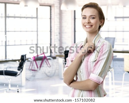 Casual female officeworker at office, smiling. - stock photo