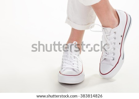 Casual footwear style for women. A pair of simple trainers. White chinos and footwear. Lacing of casual fabric shoes. - stock photo