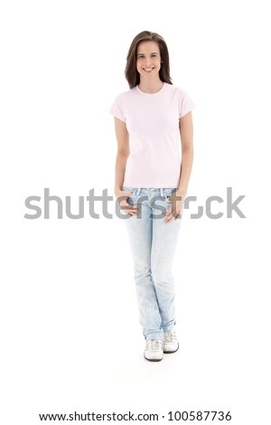 Casual full length portrait of attractive young woman standing in studio, smiling at camera.
