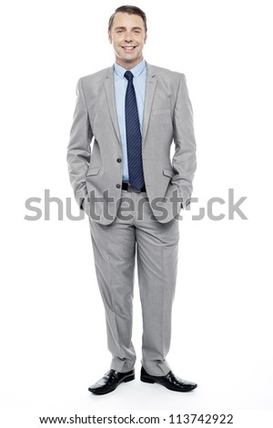 Casual full length portrait of professional businessman. Standing with hands in trousers pocket - stock photo