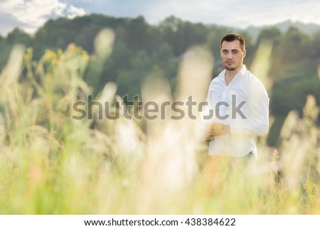 Casual gorgeous young man standing in a grass, outdoors. Male beauty natural concept with copyspace for text - stock photo