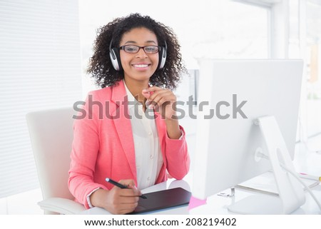 Casual graphic designer working at her desk smiling at camera in her office