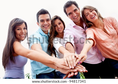 Casual group of people with hands together in the center - teamwork concepts - stock photo