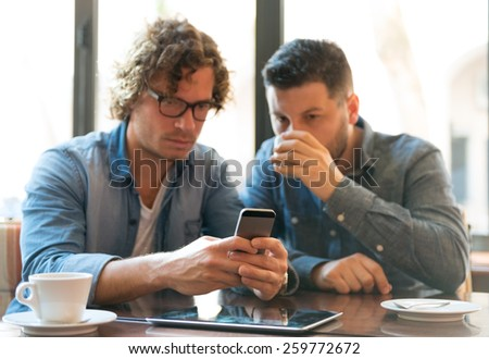 Casual guys in a Coffee Shop looking at mobile phone - stock photo