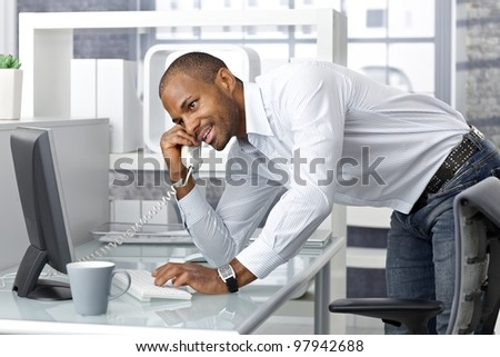 Casual happy businessman talking on landline phone in office, standing leaning on desk. - stock photo