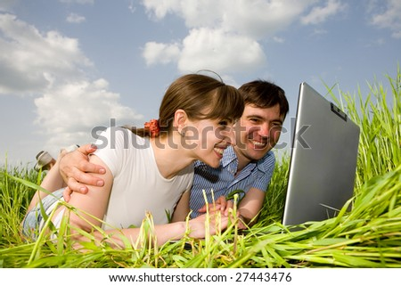 Casual happy couple on a laptop computer outdoors. Lay on the green grass. - stock photo