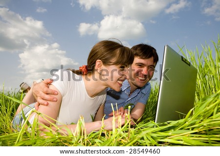 Casual happy couple on laptop computer outdoors. Lay on the green grass - stock photo