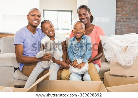 Casual happy family posing with box in living room - stock photo