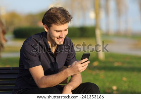 Casual happy man using a smartphone sitting on a bench in a park - stock photo