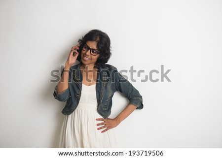 casual indian female with grey background - stock photo