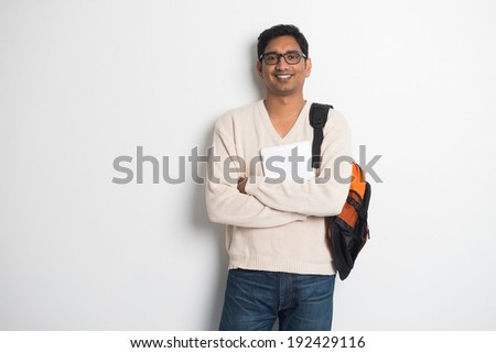 casual indian male student on a sweater and tablet - stock photo