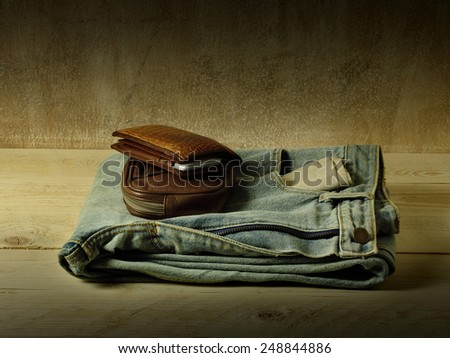 Casual jeans and leather wallet and pouch over grunge still life style - stock photo