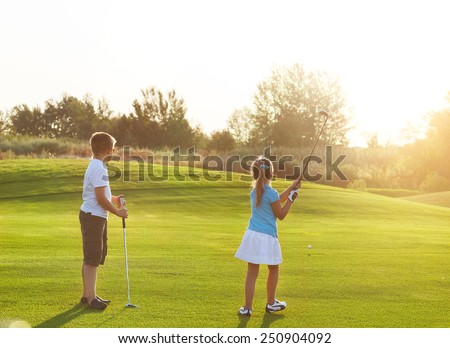 Casual kids at a golf field holding golf clubs. Sunset - stock photo