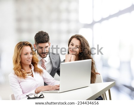 Casual lawyer working on laptop while sitting at desk with colleagues.  - stock photo