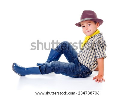 Casual little cowboy with hat, sitting on the ground - stock photo