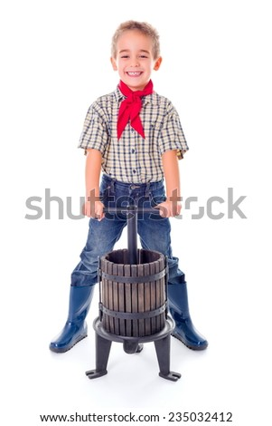 Casual little farmer boy with manual grape pressing tool - stock photo