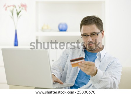 Casual man at home using laptop computer purchasing by credit card. - stock photo