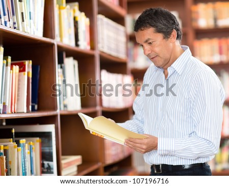 Casual man at the library reading a book - stock photo