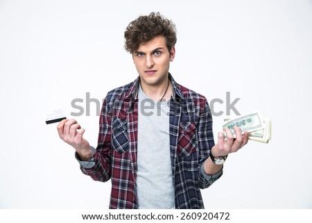 Casual man choosing between banking card or cash - stock photo