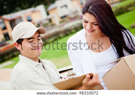 Casual man delivering a package and asking for signature - stock photo