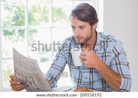 Casual man having coffee while reading newspaper at home in the living room - stock photo