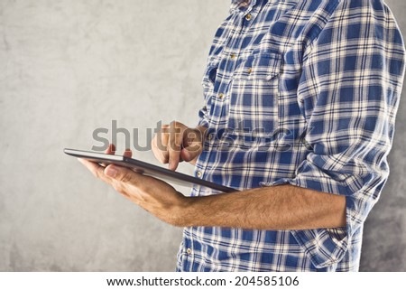 Casual man holding 10 inch display digital tablet computer and using it for internet browsing, e-book reading and other multimedial experience. - stock photo