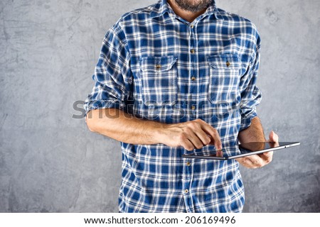 Casual man holding 10 inch display digital tablet computer and using it for internet browsing, e-book reading and other multimedia experience. - stock photo