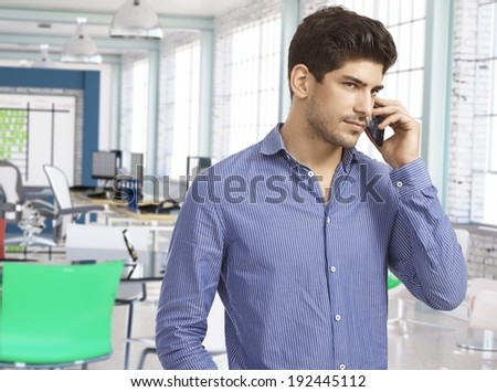 Casual man on the phone at work in modern office. - stock photo