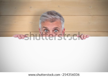 Casual man showing a poster against bleached wooden planks background - stock photo