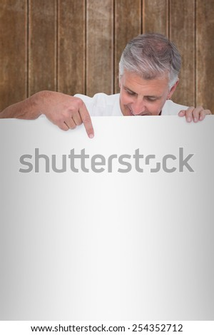Casual man showing a poster against wooden planks background - stock photo