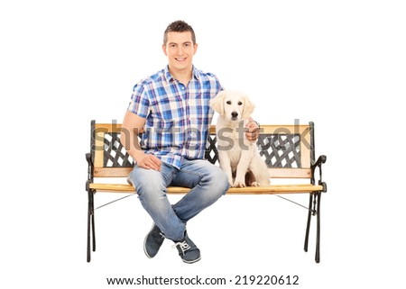 Casual man sitting on a bench with a puppy isolated on white background