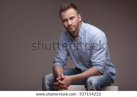 Casual man sitting on a cube isolated over a grey gradient background - stock photo