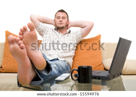 casual man sitting on sofa with laptop - stock photo