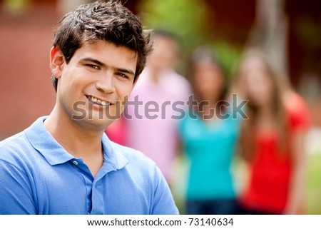 Casual man smiling outdoors with a group behind him - stock photo