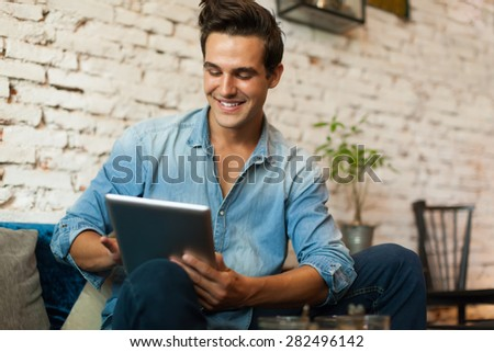 Casual Man Using Tablet Computer Smile Sitting in Cafe Surfing Internet - stock photo