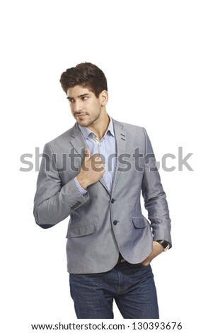 Casual man walking in jeans and jacket with hand in pocket, looking away. - stock photo