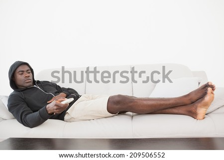 Casual man watching tv on his sofa at home in the living room - stock photo