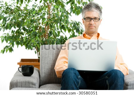 Casual man wearing jeans, orange shirt and glasses using laptop computer at home, sitting on couch. Green potted plant in the background.