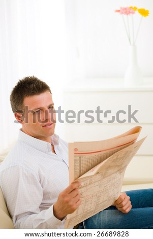 Casual man wearing white shirt and jeans, sitting on couch and reading newspaper. - stock photo