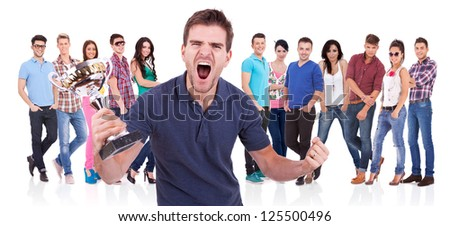casual man winning a trophy and screaming of joy in front of his friends - stock photo