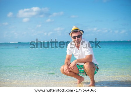 casual man with hat and sunglasses standing crouched on a tropical beach and looks at the camera - stock photo